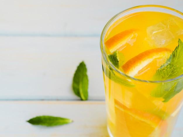 Szklanka zroszonego soku pomarańczowego z plastrami i miętą