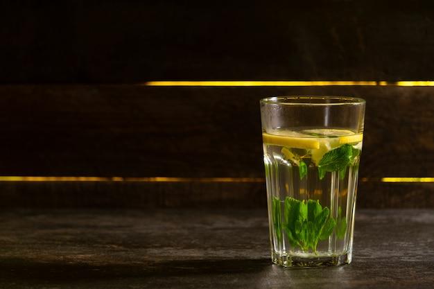 Szklankę napoju cytrynowego na drewnianej powierzchni