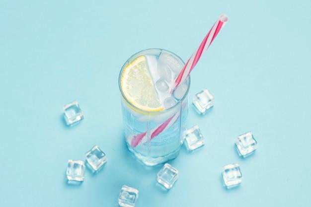 Szklankę wody lub napój z lodem i cytryną na niebieskiej powierzchni z kostkami lodu. pojęcie gorącego lata, alkohol, napój chłodzący, gasi pragnienie. leżał płasko, widok z góry