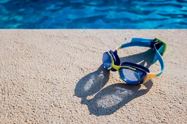 Szklanki basenowe na brzegu wody z miejscem na kopię w słoneczny dzień.