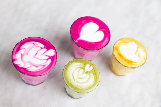 Szklanki buraków, matcha, latte z kurkumą na tle marmurowego stołu. modne zdrowe napoje.