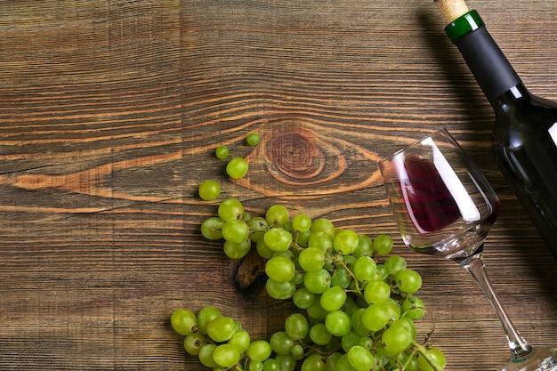Szklanki butelka czerwonego wina i winogron na drewnianym stole
