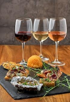 Szklanki czerwonego, różowego i białego wina z różnymi rodzajami zimnych przekąsek. koncepcja żywności i napojów.