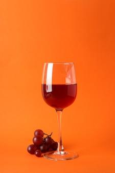 Szklanki czerwonego wina i winogron na pomarańczowym tle