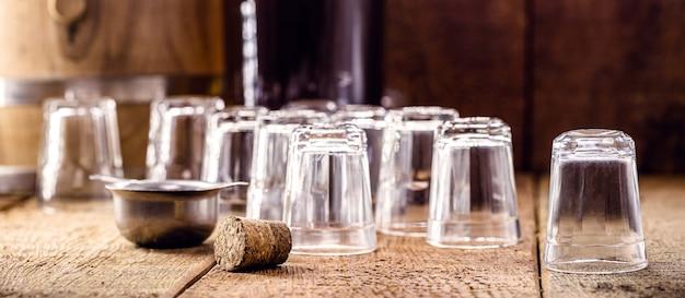 Szklanki do napojów, puste szklane kubki na małe dawki, na drewnianym stole