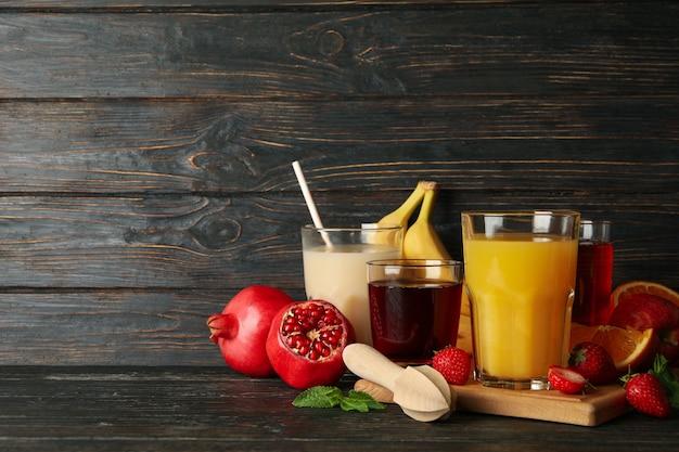 Szklanki i słoiki z różnymi sokami na drewnianym