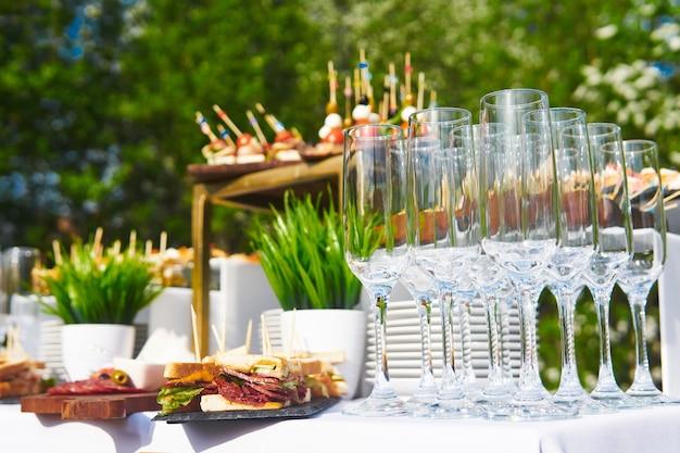 Szklanki, kanapki i zimne przekąski na stole w oczekiwaniu na rozpoczęcie bufetu na świeżym powietrzu