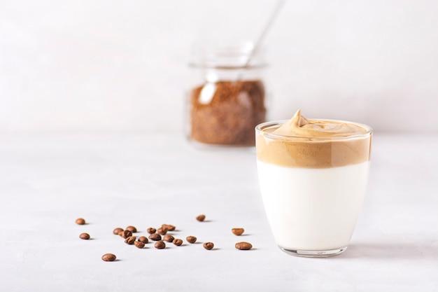 Szklanki kawy dalgona i puszka kawy rozpuszczalnej stoją na szarym betonowym stole.