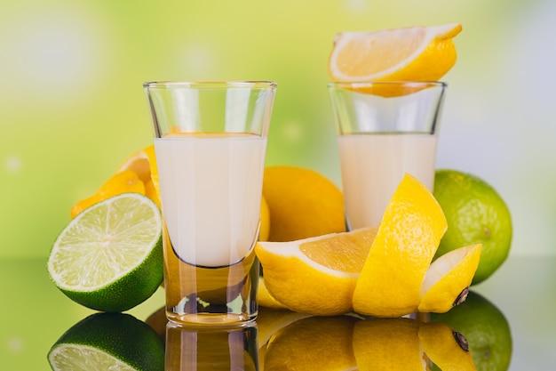 Szklanki likieru śmietankowego z limonką i cytryną na zielonym tle z odbiciem. brak likieru cytrynowego. tradycyjny włoski napój alkoholowy limoncello