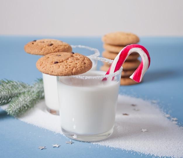 Szklanki mleka, ciastka, trzciny cukrowej, gałąź choinki na niebiesko