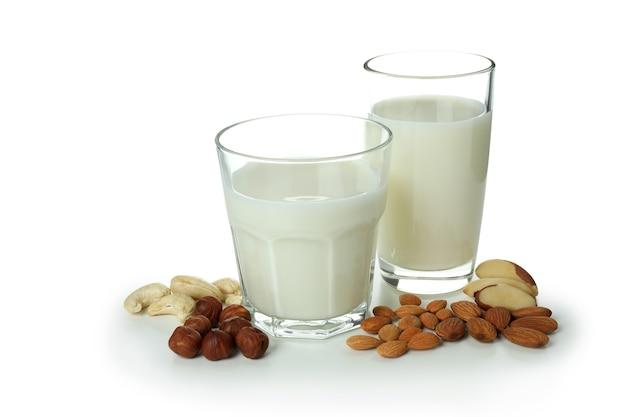 Szklanki mleka i orzechów na białym tle