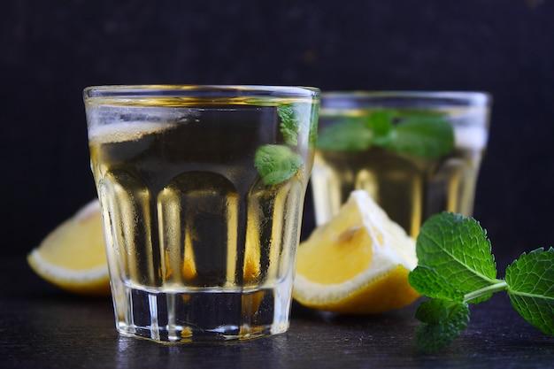 Szklanki napoju alkoholowego z cytryną i miętą, shaker