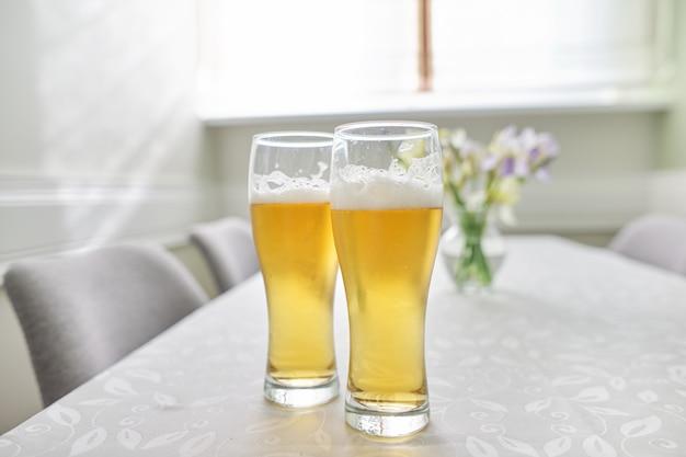 Szklanki piwa na stole, domowy stół z krzesłami w pobliżu okna