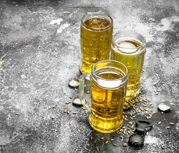Szklanki piwa z otwieraczem do butelek i korkami na rustykalnym stole.