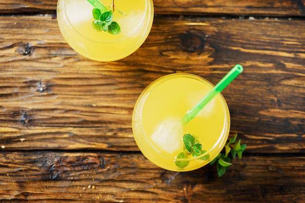 Szklanki pomarańczowych koktajli z lodem i miętą, drewnianym stołem i selektywną ostrością