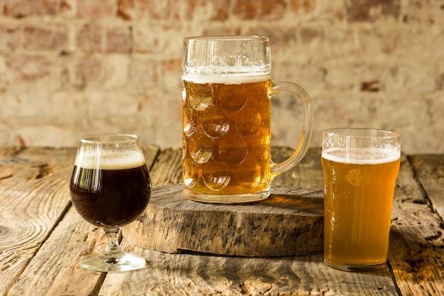 Szklanki różnych rodzajów ciemnego i jasnego piwa na drewnianym stole w kolejce. zimne pyszne drinki przygotowane na przyjęcie dużego przyjaciela. koncepcja drinków, zabawy, spotkania, oktoberfest.
