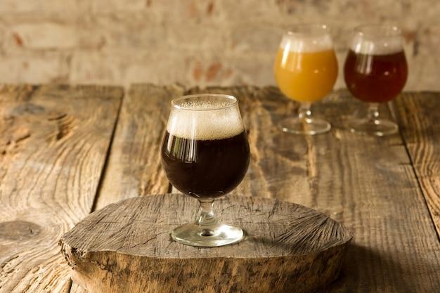 Szklanki różnych rodzajów ciemnego i jasnego piwa na drewnianym stole w kolejce. zimne pyszne drinki są przygotowane na przyjęcie dużego przyjaciela. koncepcja drinków, zabawy, spotkania, oktoberfest.