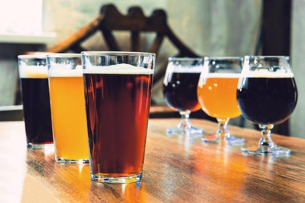 Szklanki różnych rodzajów ciemnego i jasnego piwa na drewnianym stole w kolejce