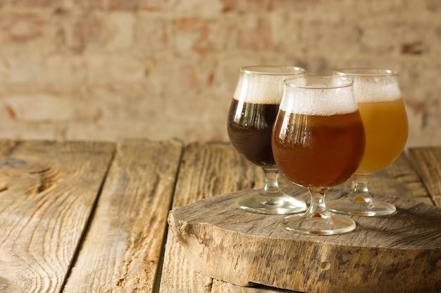 Szklanki różnych rodzajów piwa na drewnianym tle