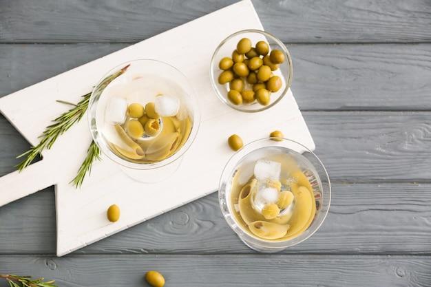 Szklanki smacznego koktajlu martini z oliwkami na stole