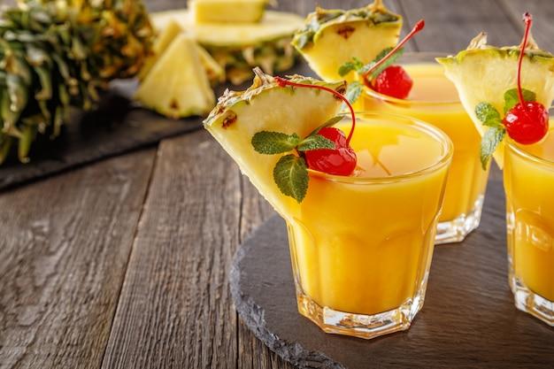 Szklanki soku ananasowego z kawałkami ananasa, koktajl wiśni i mięty