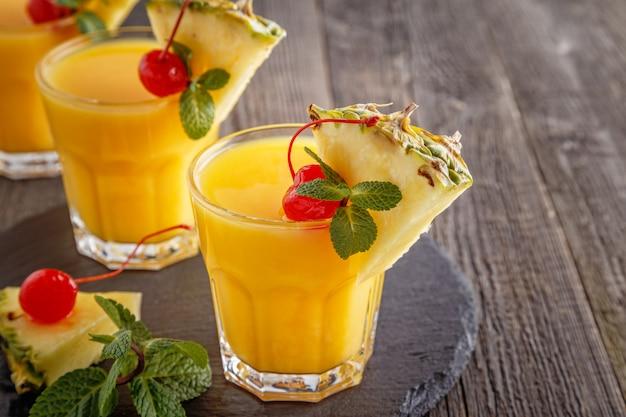 Szklanki soku ananasowego z kawałkami ananasa, wiśni koktajlowych i mięty na drewnianym stole.