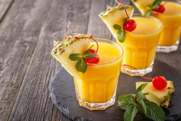 Szklanki soku ananasowego z kawałkami ananasa