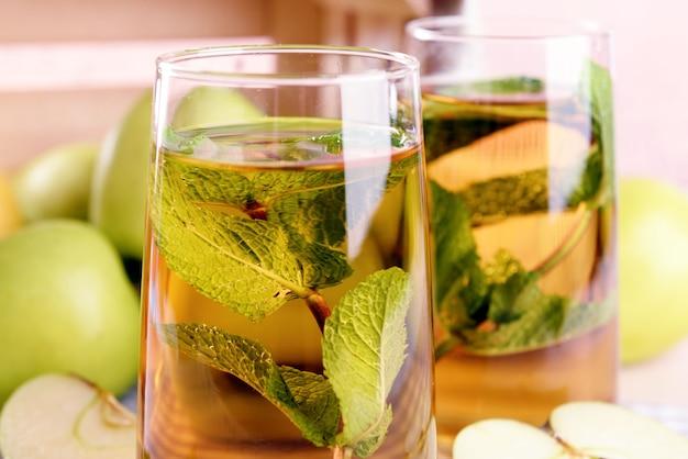 Szklanki soku jabłkowego z owocami i świeżą miętą na stole