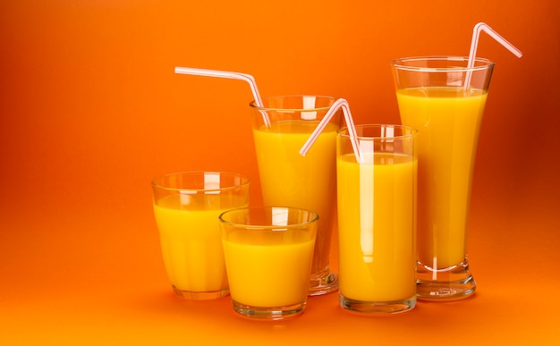 Szklanki soku pomarańczowego na kolor pomarańczowy przestrzeni