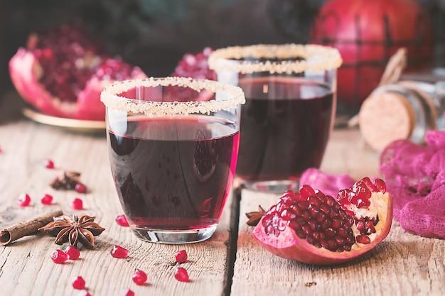 Szklanki soku z granatu ze świeżych owoców granatu na drewnianym stole
