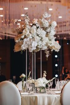 Szklanki stołowe kwiat widelec nóż podawany na kolację w restauracji o przytulnym wnętrzu
