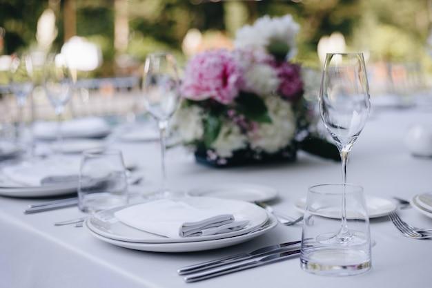 Szklanki stołowe kwiat widelec nóż podawany na kolację w restauracji z przytulnym wnętrzem