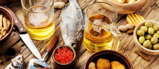Szklanki świeżego piwa i słone przekąski. kufle, ryby, piwne kiełbaski na stole