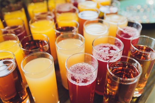 Szklanki świeżego soku na starym drewnianym stole.
