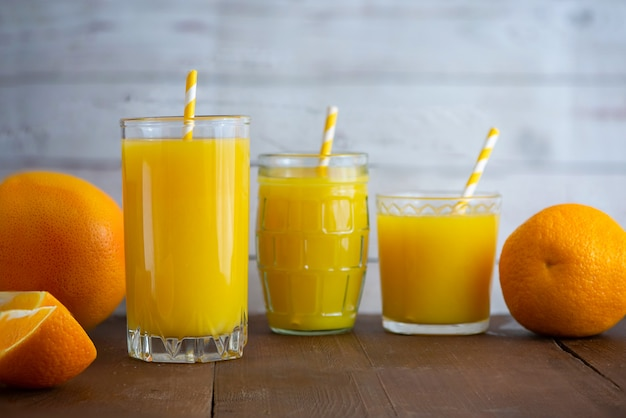Szklanki świeżego soku pomarańczowego na jasnym tle drewniane. widok z boku