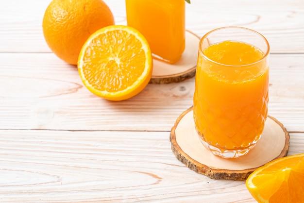Szklanki świeżego soku pomarańczowego z pomarańczami