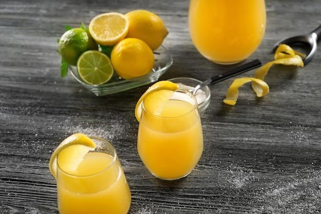 Szklanki świeżego soku z cytryny na drewnianym stole