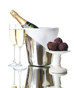 Szklanki szampana i butelka w wiadrze na jasnym tle