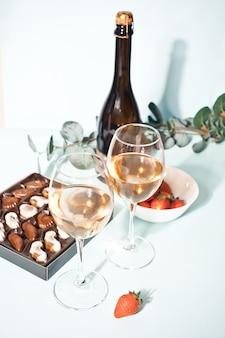 Szklanki szampana lub białego wina gronowego z tabliczką czekoladek i truskawek, butelka na tle.