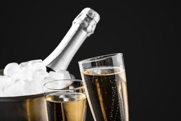 Szklanki szampana z butelką szampana w wiadrze
