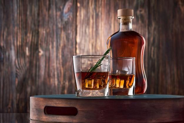 Szklanki whisky i butelka na drewnianym stole