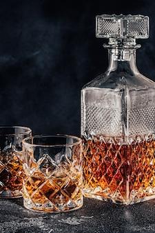Szklanki whisky z kwadratową karafką na czarnym tle kamienia.