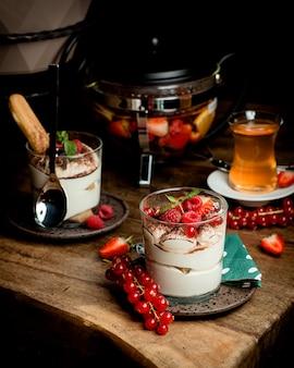 Szklanki włoskiego tiramisu przyozdobione jagodami