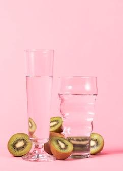 Szklanki wody i pokrojone owoce kiwi