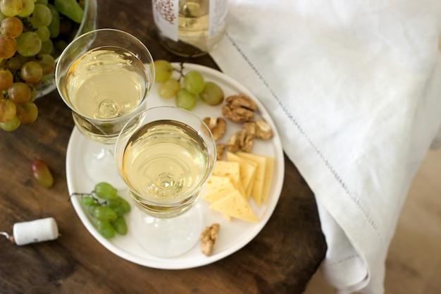 Szklanki z białym winem i butelka wina z przekąską - ser, orzechy włoskie i winogrona. styl rustykalny.