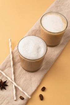 Szklanki z kawą i słomką obok