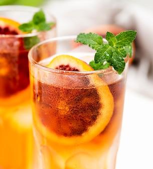 Szklanki z owocową lodową herbatą na biurku