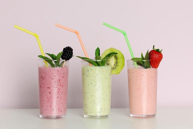 Szklanki z owocowymi koktajlami ze słomkami