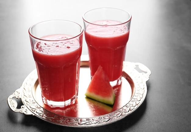 Szklanki z smoothie i plasterkiem arbuza na tacy
