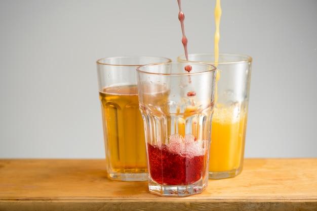 Szklanki z sokiem jabłkowym, pomarańczowym i wiśniowym